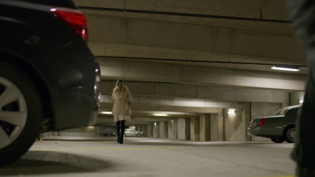 man following unsuspecting woman in underground parking garage / provo, utah, united states - provo stock videos & royalty-free footage
