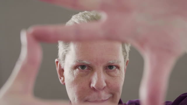 man framing his face with his hands - studio shot bildbanksvideor och videomaterial från bakom kulisserna
