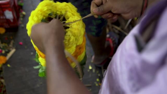 vídeos de stock e filmes b-roll de cu man from india working at floral garlands market - feirante