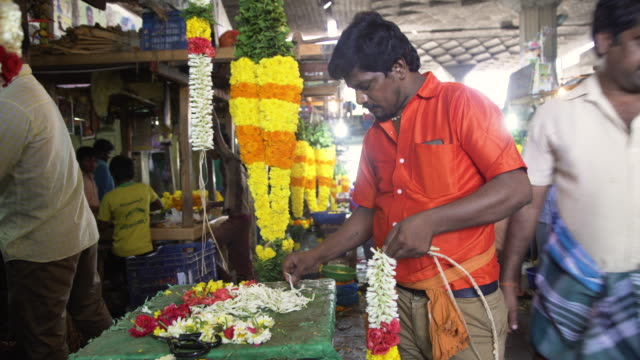 man from india working at floral garlands market - tradition stock-videos und b-roll-filmmaterial