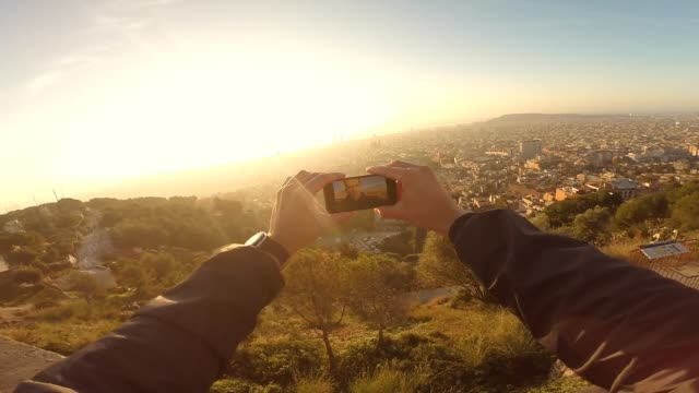 Man from personal point of view taking a selfie with the Barcelona cityscape on sunrise.
