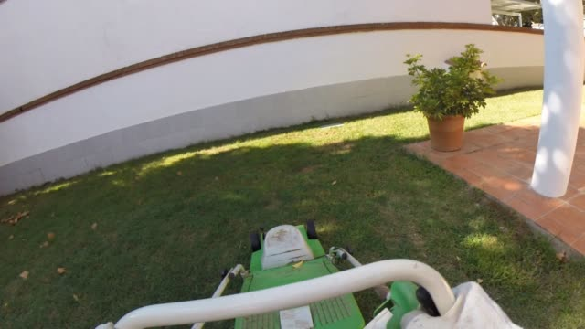Man from point of view mowing in the backyard home.