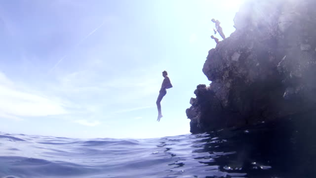 slo mo man front flipping into the sea - underwater camera stock videos & royalty-free footage