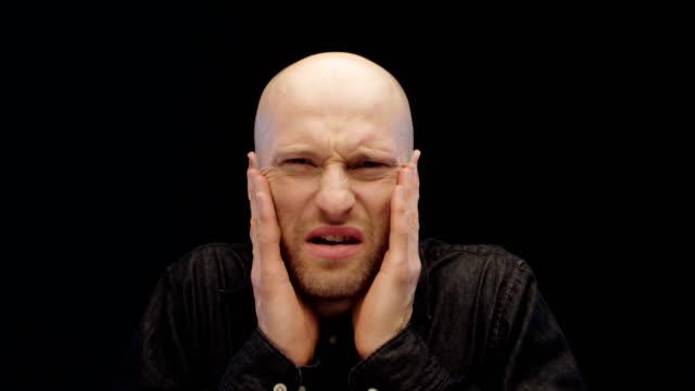 Man frowning and closing his eyes looking at imaginary, disgusting object