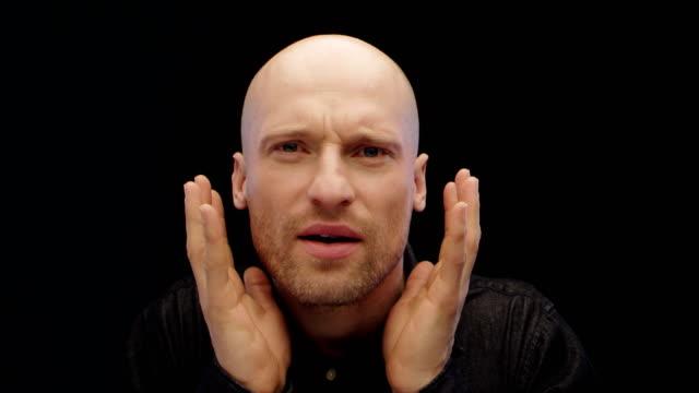 vidéos et rushes de l'homme fronçant les sourcils et en fermant les yeux en regardant un objet imaginaire, dégoûtant - touche de couleur