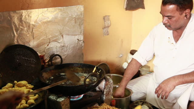 Man frying pakora in a big kadai, Delhi, India