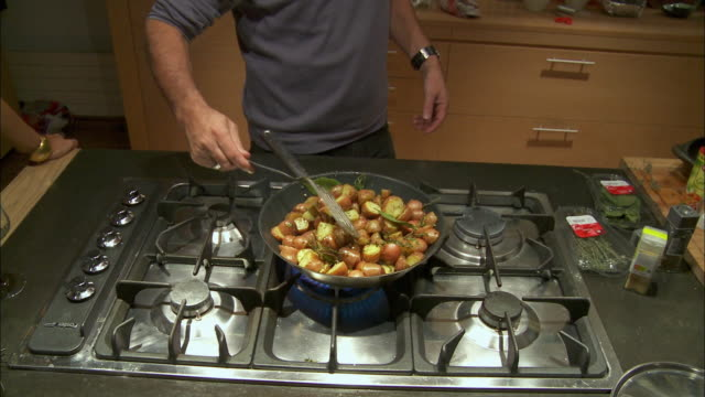 ms man frying potatoes on stove / brussels, belgium - 調理用へら類点の映像素材/bロール