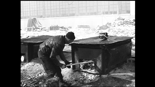 man fueling the stove with pieces of chopped wood while holding a cigarette in his mouth in the snow; factory building in the background - 1940 1949 stock-videos und b-roll-filmmaterial