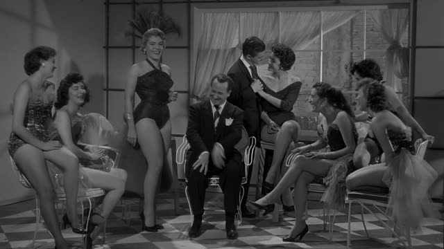 man gathered around with vedettes telling a joke, a friend behind him is flirting with woman - black and white stock videos & royalty-free footage
