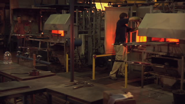 WS MS Man gathering molten glass on blowing iron and using blocking tool at glass blowing factory / Windsor, Vermont, USA