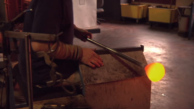 vídeos de stock, filmes e b-roll de ws ts ms man gathering molten glass on blowing iron and using blocking tool and wet newspaper to shape bowl at glass blowing factory / windsor, vermont, usa - fundir técnica de vídeo