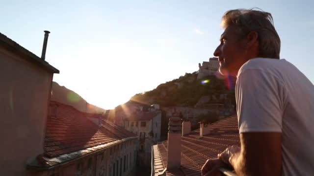 vídeos de stock, filmes e b-roll de olhares de homem varanda no piso superior, na vila medieval - parélio