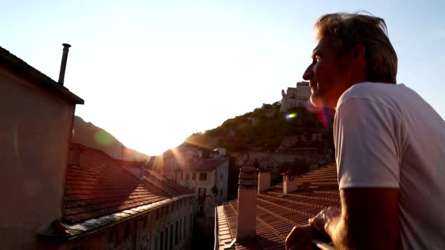 man gazes off rooftop balcony, in medieval village - sundog stock videos & royalty-free footage