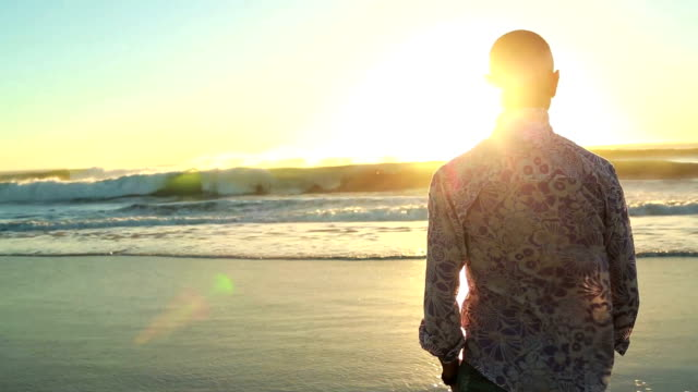 man gazes out to sea in the setting sun - contemplation stock videos & royalty-free footage
