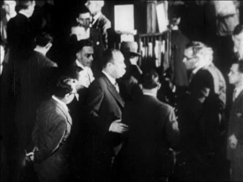 B/W 1929 man gesturing on busy floor of NY Stock Exchange / newsreel