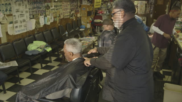 man gets haircut in barber shop, wide shot high angle - cutting hair stock videos & royalty-free footage