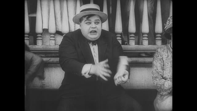 1917 man (fatty arbuckle) gets handsy with women watching horse race before shouting at boy jockey riding horse wrong way - binoculars stock videos & royalty-free footage