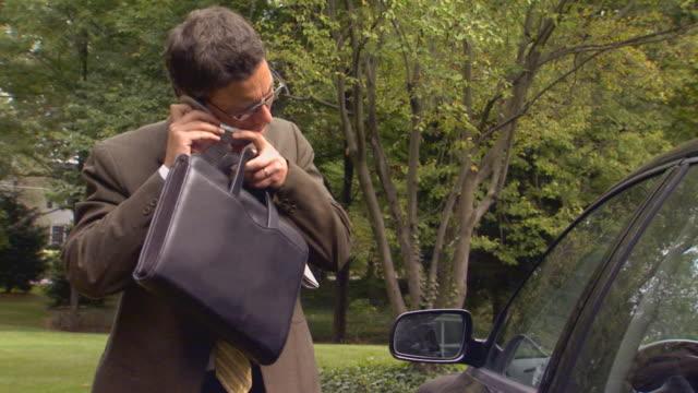 vidéos et rushes de man gets into car and drives off - chemise et cravate