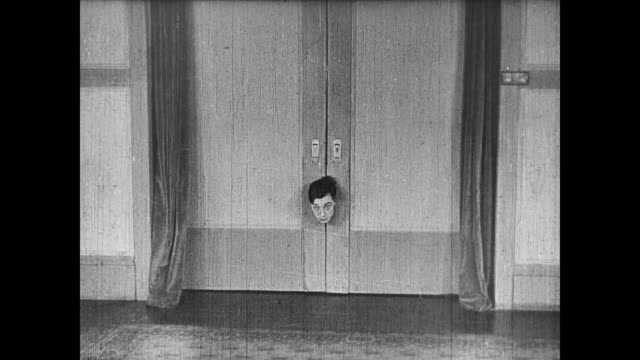 vídeos de stock, filmes e b-roll de 1922 man (buster keaton) gets neck caught in automatic door - confinamento