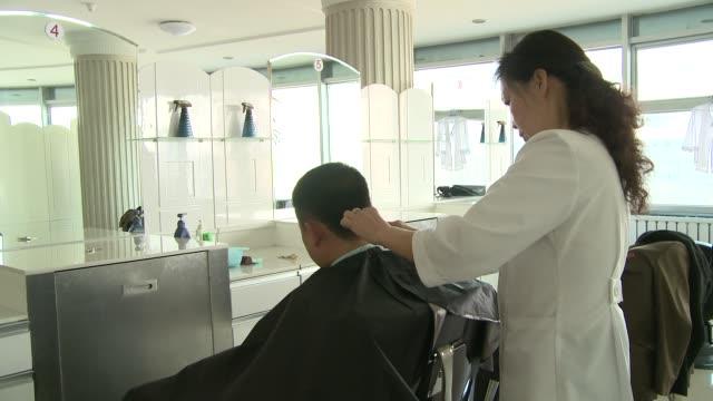 Man getting a haircut in a hair salon in North Korea