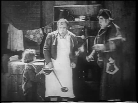 vidéos et rushes de b/w 1922 man getting angry at small orphan boy + threatening him with cane / feature - orphelin