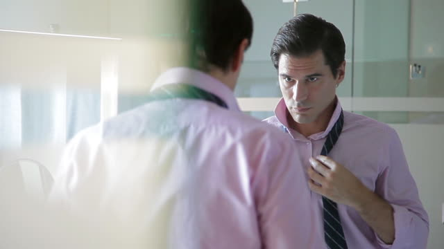 man getting dressed for the day ahead - shirt and tie stock-videos und b-roll-filmmaterial