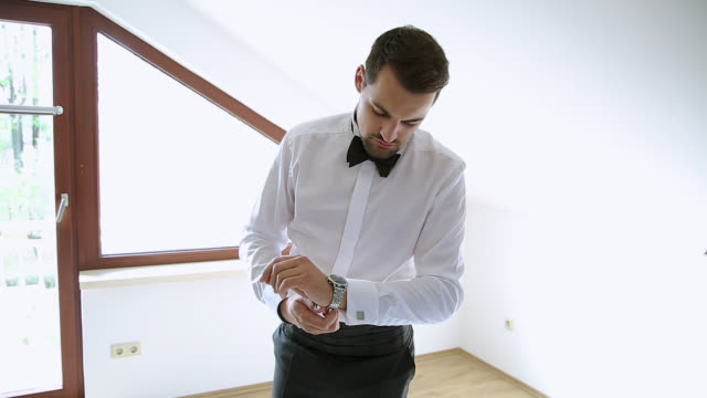 Man getting dressed, putting wrist watch on his hand
