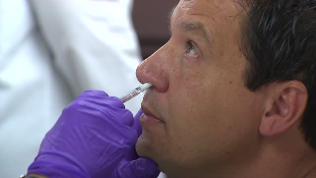 vídeos de stock, filmes e b-roll de wgn man getting h1n1 swine flu nasal spray on october 24 2013 in chicago illinois - gripe suína