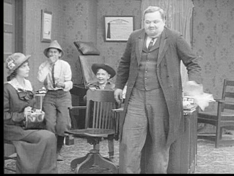 1913 b/w ms man (fatty arbuckle) getting hands stuck on sticky paper / usa - 1913 stock-videos und b-roll-filmmaterial