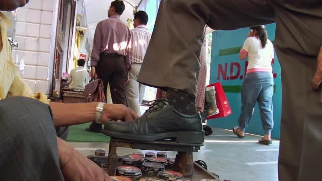 ms man getting his shoe polished / delhi, india - 説得点の映像素材/bロール