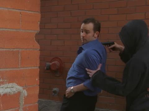 vídeos de stock e filmes b-roll de man getting mugged at gunpoint - só homens de idade mediana