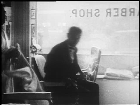 b/w 1925 man getting out of barber's chair + woman takes his place / newsreel - 1925 stock videos & royalty-free footage