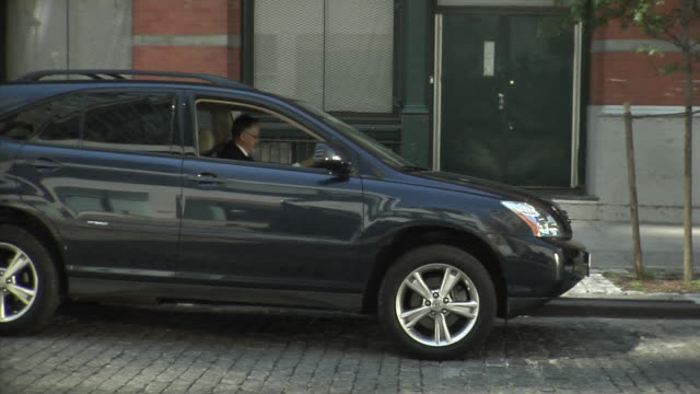 ms man getting out of suv and walking away, tribeca, new york, usa - suv点の映像素材/bロール