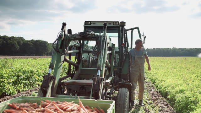 MS Man getting out of tractor at organic farm and walking to meet woman / Brodowin, Brandenburg, Germany