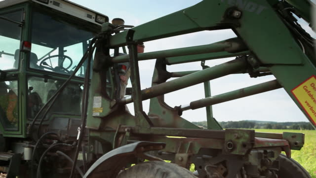 ms pan man getting out of tractor at organic farm and walking to meet woman / brodowin, brandenburg, germany - tractor stock videos & royalty-free footage