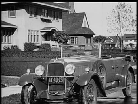 b/w 1928 man getting out of vauxhall convertible / industrial - 1928 stock-videos und b-roll-filmmaterial