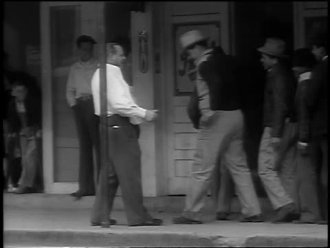 stockvideo's en b-roll-footage met b/w 1939 man getting punched in stomach by line of men entering restaurant / kennedy, tx - menselijke buik
