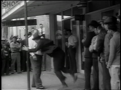 b/w 1939 man getting punched in stomach by line of men entering restaurant / kennedy, tx - belly punching stock-videos und b-roll-filmmaterial