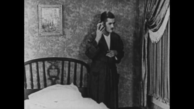 stockvideo's en b-roll-footage met 1925 man getting ready for bed bangs alarm clock against wall to test if it's working - 1925