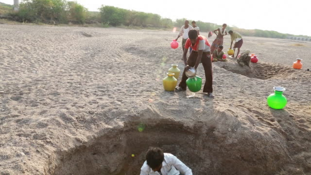 Man getting water out of and almost empty waterhole, group of people waiting, near Pannur, India