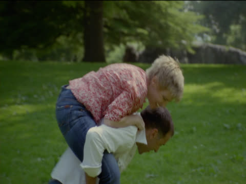 man gives a woman a piggyback ride in central park, new york - giovane nell'animo video stock e b–roll