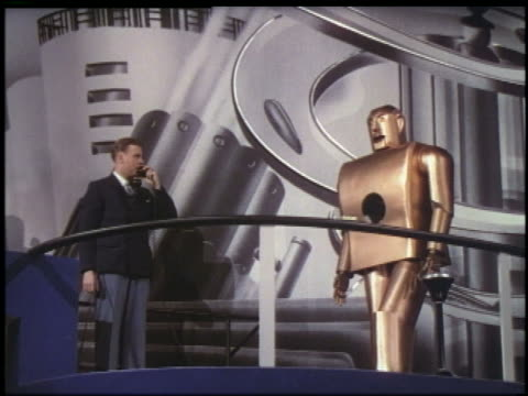 vídeos de stock e filmes b-roll de 1939 man gives commands to robot with telephone robot walks / ny world's fair - 1939