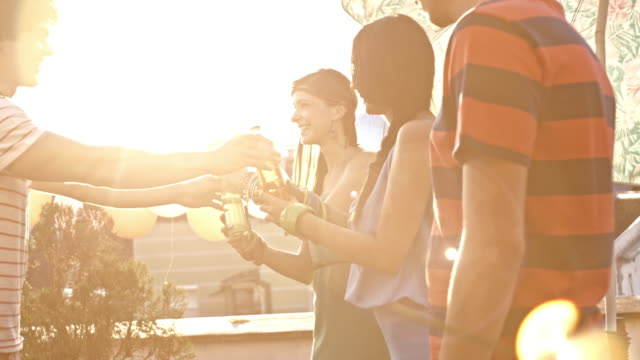 Man gives drinks to his friends during rooftop party
