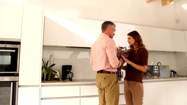 Man gives woman a bunch of flowers in Kitchen
