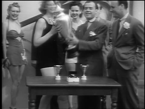 b/w 1941 man gives woman with bathing suit large trophy in swimsuit contest / palisades park nj - spielkandidat stock-videos und b-roll-filmmaterial