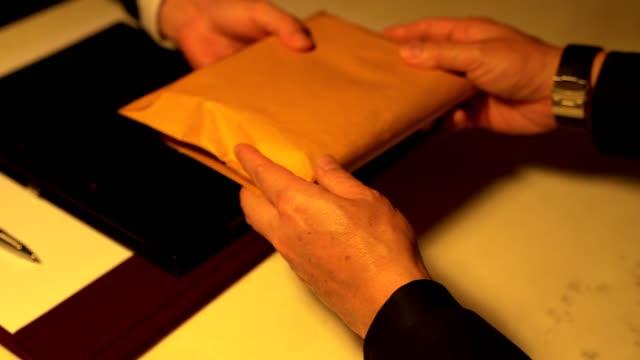 stockvideo's en b-roll-footage met een man geven omkopen geld in een bruine envelop naar een andere zakenman in een corruptie scam - omkoping