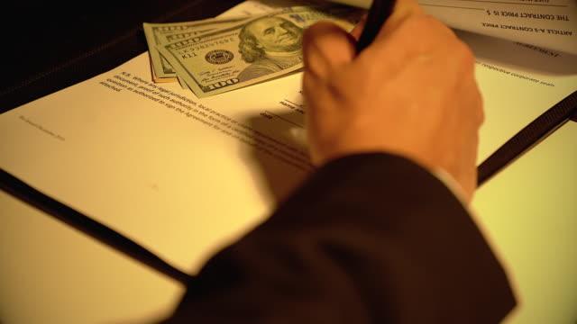 ein mann, der einem anderen geschäftsmann bestechungsgelder in einem korruptionsbetrug gibt - bestechung stock-videos und b-roll-filmmaterial