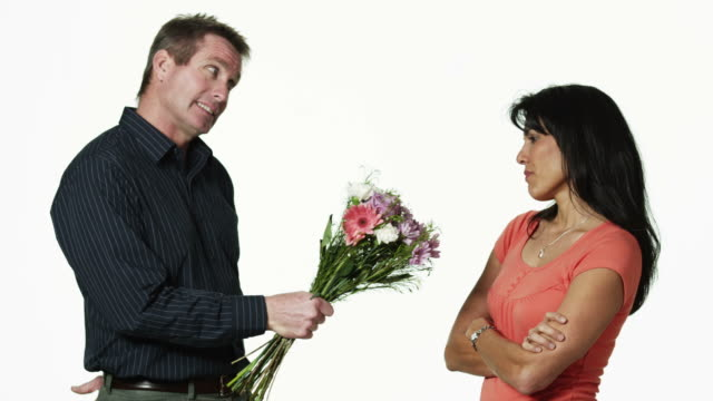 MS Man giving flowers to woman, against white background / Orem, Utah, USA