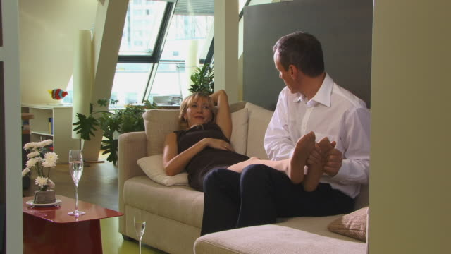 vídeos y material grabado en eventos de stock de ms, man giving foot massage to woman lying on sofa, berlin, germany - massage room