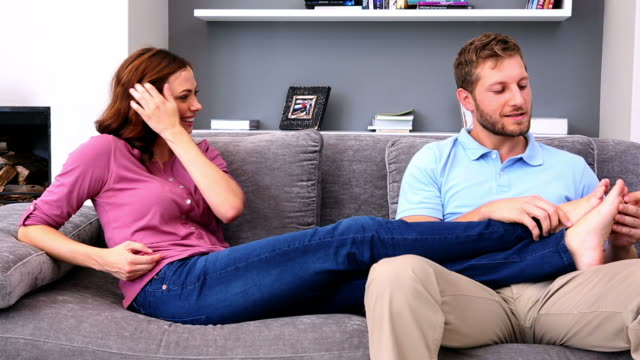 man giving his partner a foot rub - legs crossed at ankle stock videos and b-roll footage